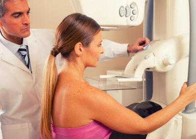 Male doctor checking mammography machine scan with patient woman